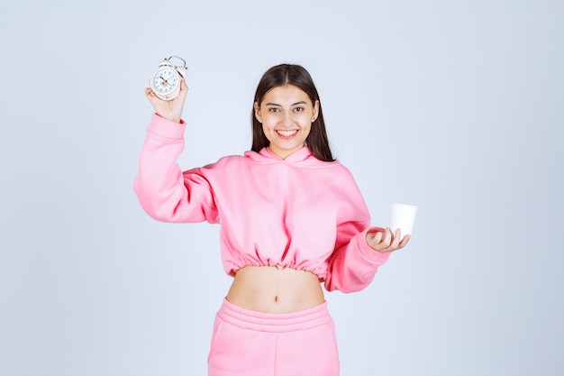 Dziewczyna w różowej piżamie trzyma budzik i filiżankę kawy.