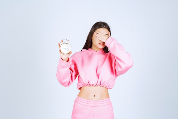 Dziewczyna w różowej piżamie trzyma budzik i wygląda na śpiącą.
