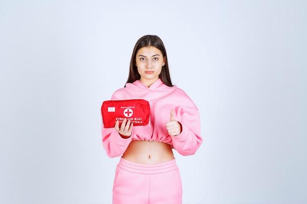 Dziewczyna w różowej piżamie trzyma czerwoną apteczkę i ją promuje.