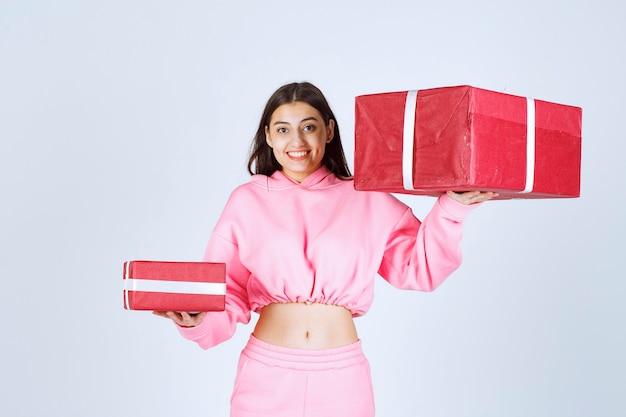 Dziewczyna w różowej piżamie trzyma duże i małe czerwone pudełka na prezenty i uśmiecha się.
