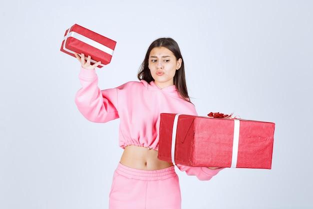 Dziewczyna w różowej piżamie trzyma duże i małe czerwone pudełka na prezenty i wygląda na niezadowoloną.