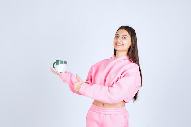 Dziewczyna w różowej piżamie trzyma kubek kawy i czuje się szczęśliwa.