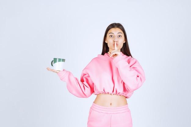 Dziewczyna w różowej piżamie trzyma kubek kawy i prosi o ciszę.