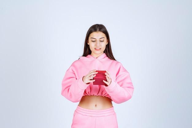 Dziewczyna w różowej piżamie trzyma małe czerwone pudełko.