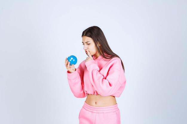 Dziewczyna w różowej piżamie trzyma mini kulę ziemską i myśli.