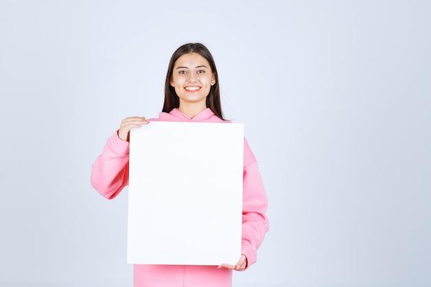 Dziewczyna w różowej piżamie trzyma przed sobą pustą kwadratową tablicę prezentacji.