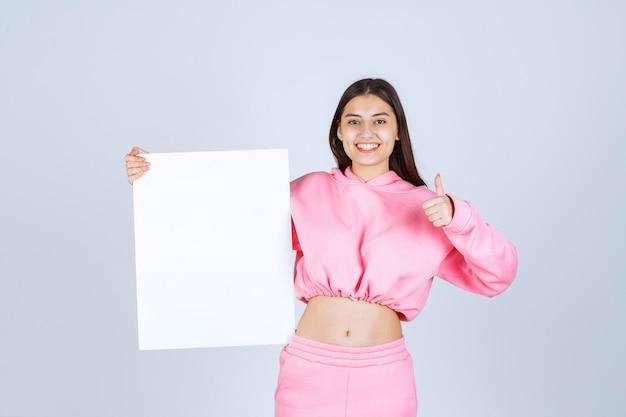 Dziewczyna w różowej piżamie trzyma pustą kwadratową tablicę prezentacji i pokazuje kciuk do góry znak.