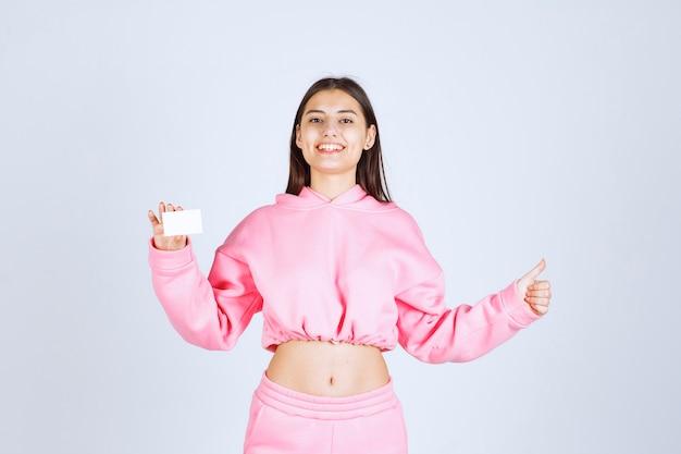 Dziewczyna w różowej piżamie trzyma wizytówkę i pokazuje radość znak ręką.