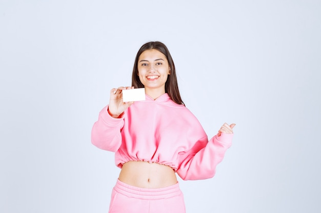 Dziewczyna w różowej piżamie trzyma wizytówkę i wskazuje na kogoś innego.