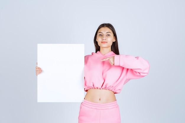 Dziewczyna w różowej piżamie trzymając pustą kwadratową tablicę prezentacji i wskazując na nią.