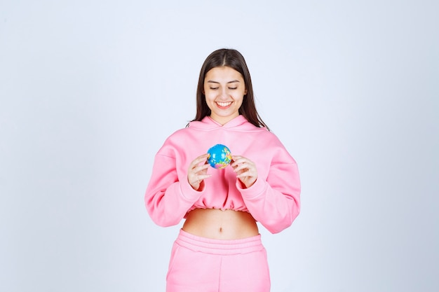 Dziewczyna w różowej piżamie trzymając w ręku mini kulę ziemską.