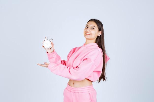 Dziewczyna W Różowej Piżamie Trzymająca Budzik I Promująca Go Jako Produkt. Darmowe Zdjęcia