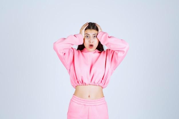 Dziewczyna w różowej piżamie trzymająca głowę, gdy jest wyczerpana lub ma ból głowy.
