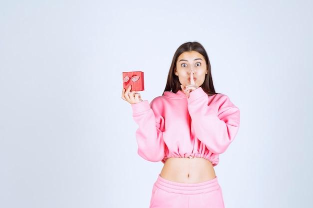 Dziewczyna w różowej piżamie trzymająca małe czerwone pudełko i prosząca o ciszę.