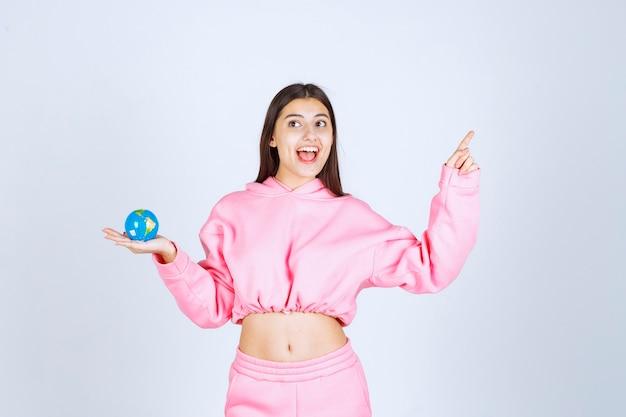Dziewczyna w różowej piżamie trzymająca mini kulę ziemską wskazującą gdzieś w górę.