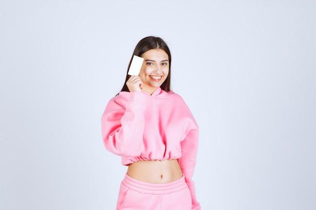 Dziewczyna w różowej piżamie trzymająca wizytówkę i przedstawiająca się swoim partnerom biznesowym.
