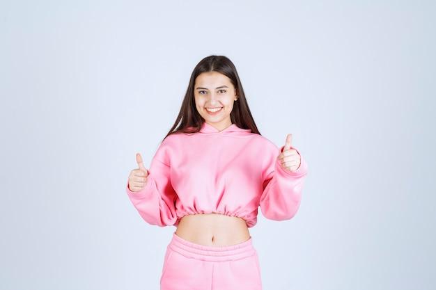 Dziewczyna w różowej piżamie, uśmiechając się i ciesząc się czymś.