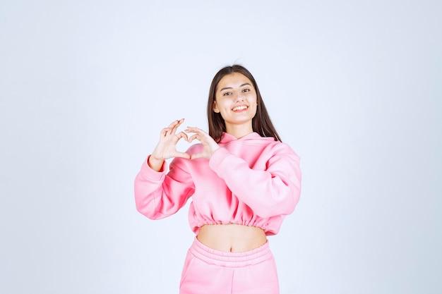 Dziewczyna w różowej piżamie wieje miłość