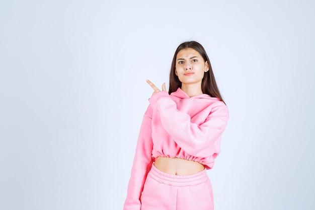 Dziewczyna w różowej piżamie wskazując na coś po lewej stronie