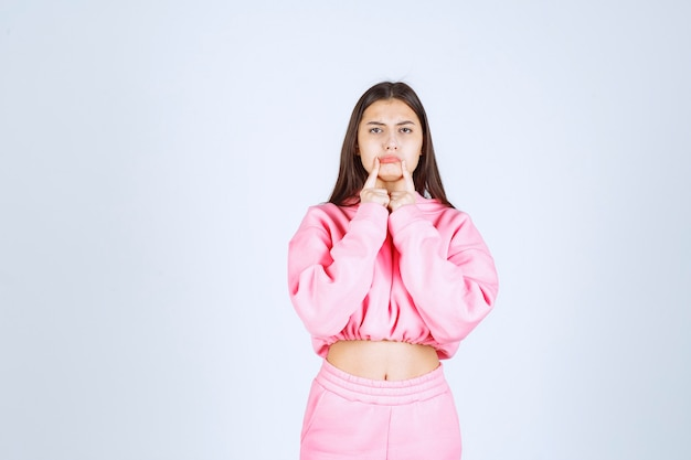 Dziewczyna w różowej piżamie, wskazując na usta