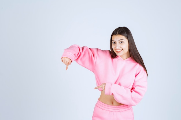Dziewczyna w różowej piżamie, wskazując poniżej
