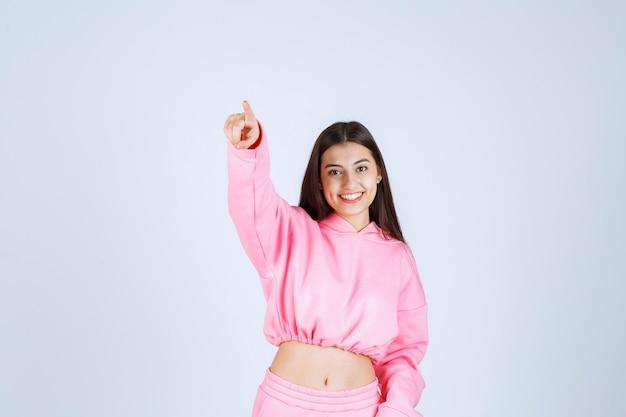 Dziewczyna w różowej piżamie wskazująca gdzieś.