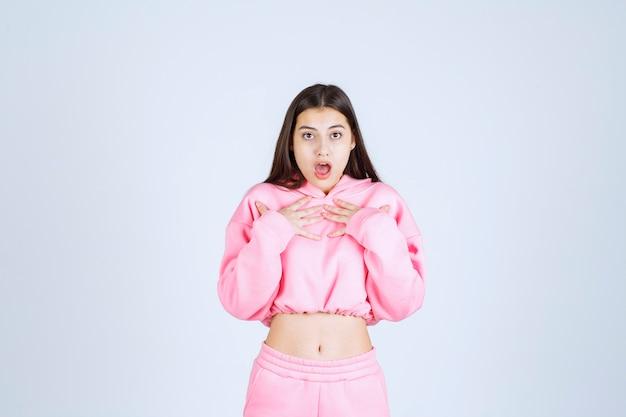 Dziewczyna w różowej piżamie wskazuje na siebie i wygląda na zaskoczoną.