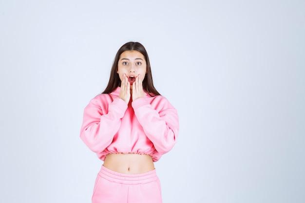 Dziewczyna w różowej piżamie wygląda na przestraszoną i przerażoną