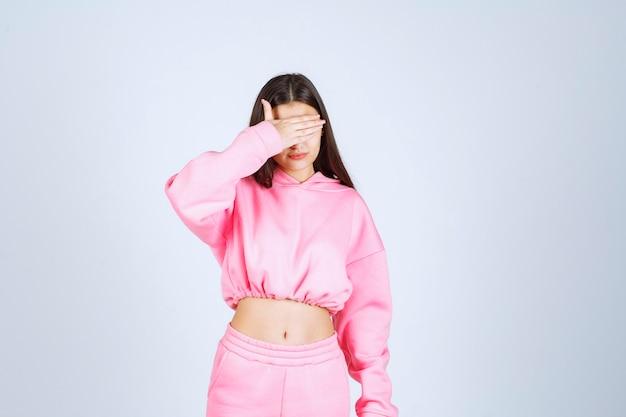 Dziewczyna w różowej piżamie wygląda na przestraszoną i przestraszoną