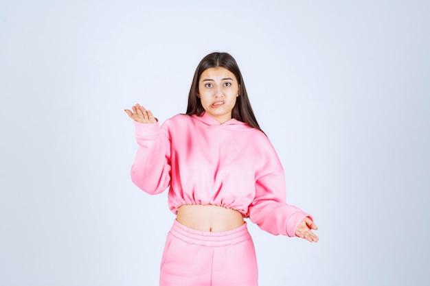 Dziewczyna w różowej piżamie wygląda na zagubioną i zamyśloną