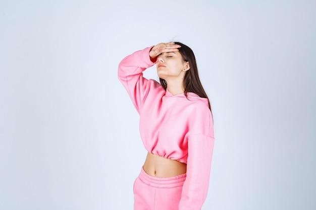 Dziewczyna w różowej piżamie wygląda na zmęczoną i śpiącą
