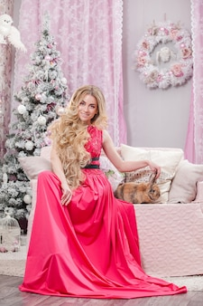 Dziewczyna w różowej sukience na tle bożego narodzenia w kolorze różowym.