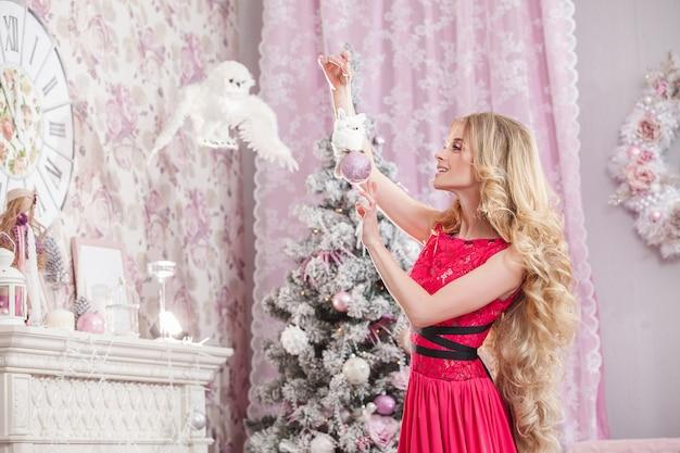 Dziewczyna w różowej sukience ozdabia choinkę