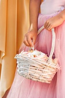 Dziewczyna w różowej sukience trzyma biały wiklinowy kosz z płatkami róż. ślub