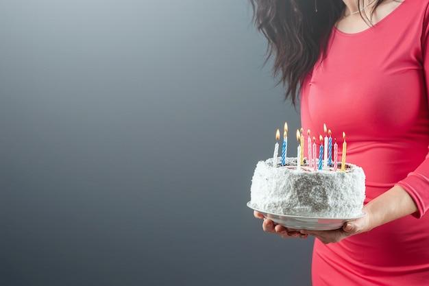 Dziewczyna w różowej sukience trzyma w rękach ciasto z płonącymi świecami, zbliżenie. gratulacje z okazji urodzin. skopiuj miejsce