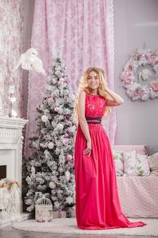 Dziewczyna w różowej sukience w domu na boże narodzenie