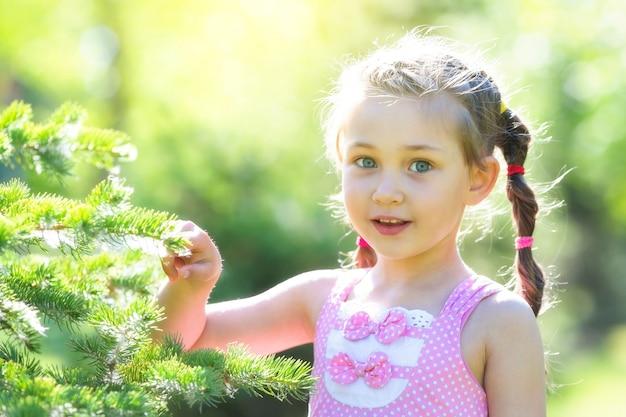 Dziewczyna w różowej sukience w lesie.