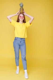 Dziewczyna w różowych okularach z ananasem na głowie na żółtej ścianie