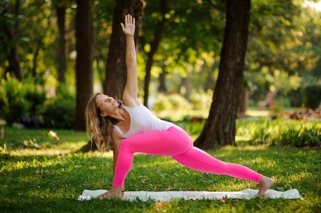 Dziewczyna w różowym kombinezonie uprawiania jogi w parku w pozie extended side angle pose