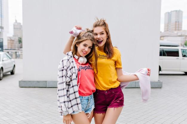 Dziewczyna w różowym podkoszulku i koszuli w kratkę chętnie pozuje obok podekscytowanej przyjaciółki w żółtym stroju przed białą ścianą