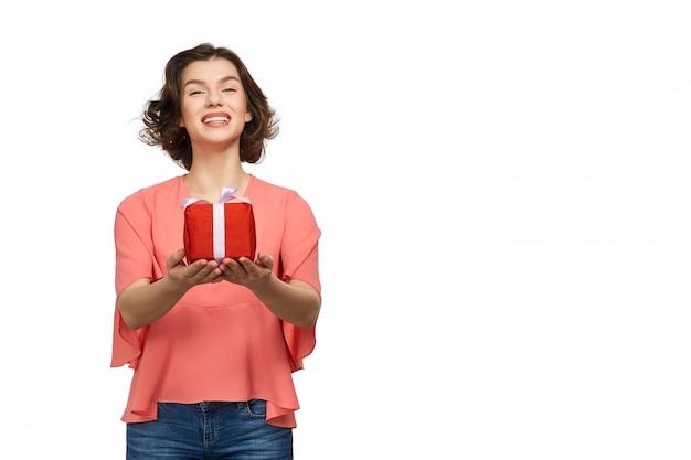 Dziewczyna w różowym swetrze i dżinsach trzyma prezent