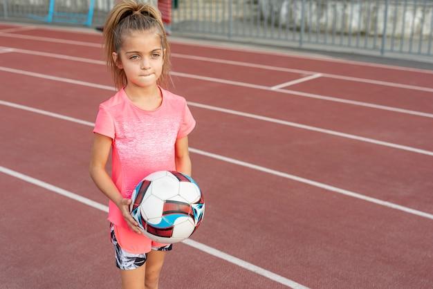 Dziewczyna w różowym t-shirt gospodarstwa piłki nożnej