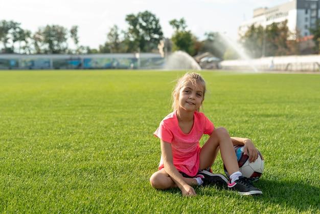 Dziewczyna w różowym t-shirt siedzi na boisku piłkarskim