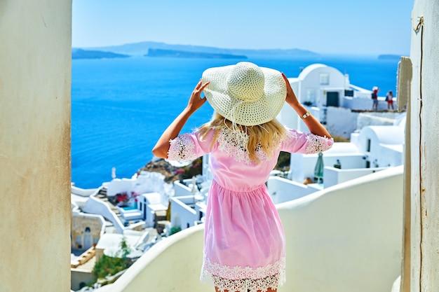 Dziewczyna w różowym z słomkowym kapeluszu, widok z tyłu w oia, santorini, grecja wyspa. turystyczna dziewczyna w europie