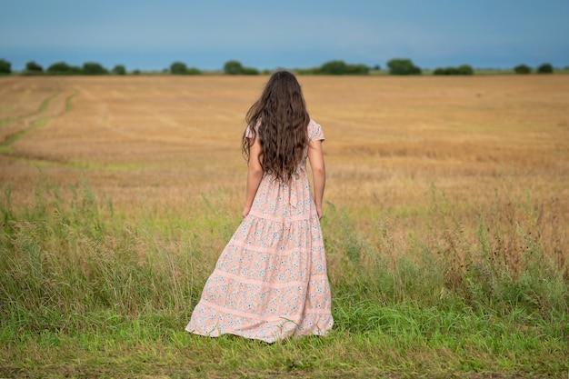Dziewczyna w rustykalnej sukience z długimi włosami stoi tyłem do aparatu i patrzy na świeżo ścięte i zebrane pole.