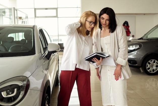 Dziewczyna w salonie samochodowym kupuje mały miejski samochód.