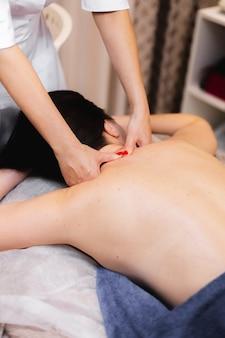 Dziewczyna w salonie spa otrzymuje masaż pleców i karku, leży przy stole kosmetycznym, jest zrelaksowana i cieszy się tym procesem