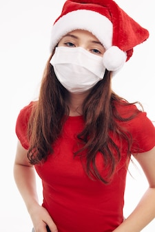 Dziewczyna w santa hat czerwona koszulka maska medyczna nowy rok studio