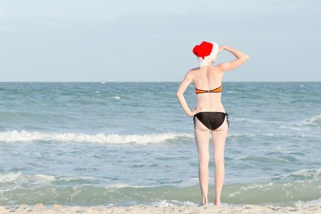 Dziewczyna w santa hat i kostiumie kąpielowym wygląda w dal. brzeg morza.