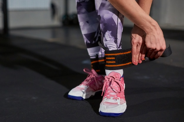 Dziewczyna w siłowni na tle betonowej ściany mocuje nogę na elastycznym bandażu.